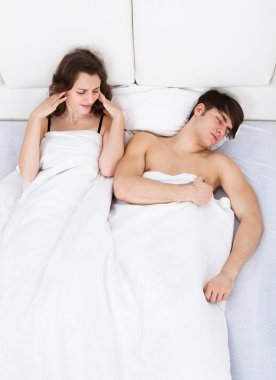 Woman Suffering From Headache While Man Snoring In Bed