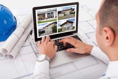 Male architect looking at designs of house on laptop at office stock vector