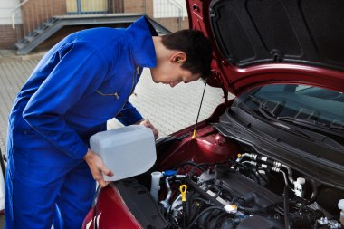 Mechanic Pouring Antifreeze Into Windscreen Water Tank