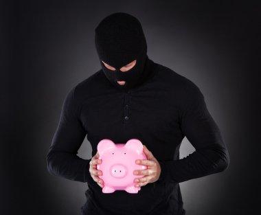 Burglar stealing a pink piggy bank
