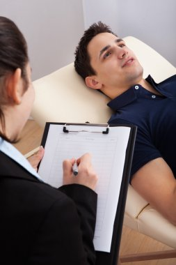Patient Communicating While Psychologist Writing Notes