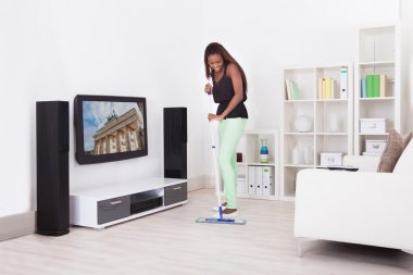 African American woman cleaning floor in living room