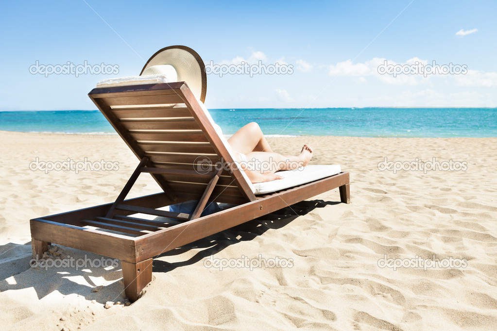 Etonnant Woman Sunbathing On Deck Chair At Beach U2014 Stock Photo