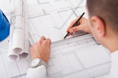 Architect Working On Blueprint Design