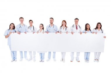 Large group of doctors and nurses with a banner