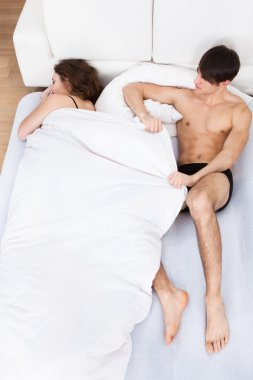 Shirtless young man pulling duvet from sleeping woman in bed at home stock vector