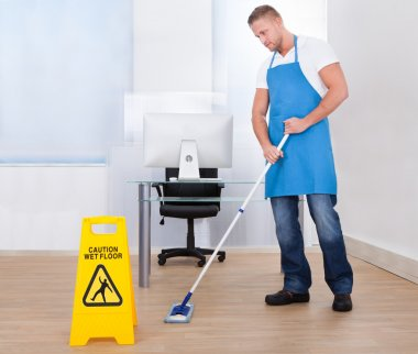 Warning notice as a janitor mops the floor