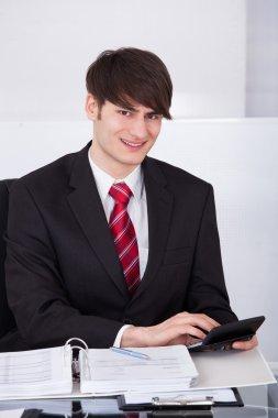 Businessman Calculating Finance Using Calculator At Desk