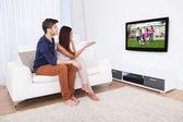 Fotografie dívat se na televizi v obývacím pokoji pár