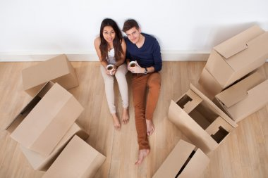 Couple Having Coffee On Floor In New Home