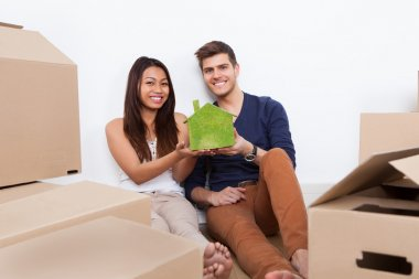 Couple Holding Green House Model At New Home