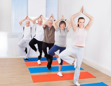 People Practicing Yoga In Tree Position At Gym