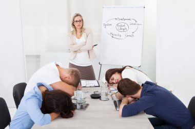 Businesswoman Looking At Colleagues Sleeping During Presentation