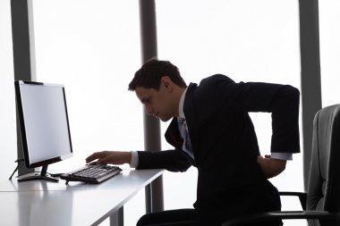 бизнесмен страдает от болей в спине в офисе
