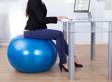 Businesswoman Working While Sitting On Pilates Ball