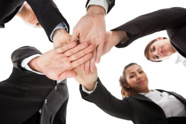Low angle view of businesspeople stacking hands against white background stock vector