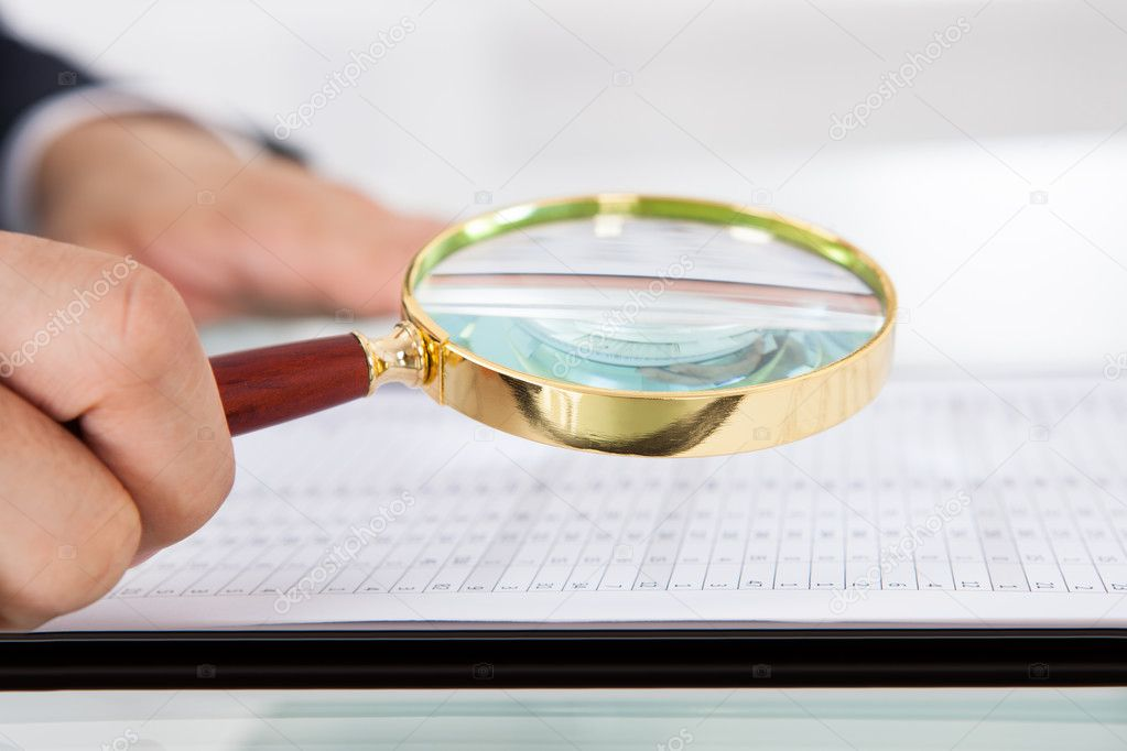 Businessman Examining Audit With Magnifying Glass In Office