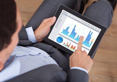 Businessman Comparing Graphs On Digital Tablet