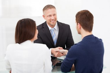 Advisor Shaking Hand With Couple