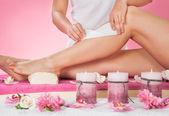 terapeut voskování nohy zákazníka v lázních