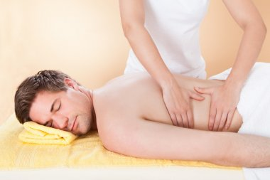 Man Receiving Back Massaging In Spa