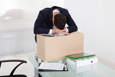 Tired Businessman Resting On Cardboard Box At Desk
