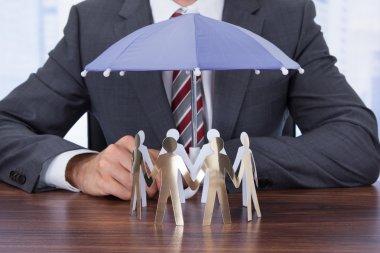 Businessman Sheltering Paper People