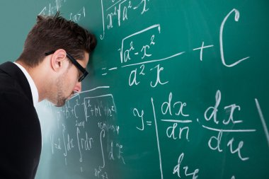 Professor Leaning Head On Blackboard