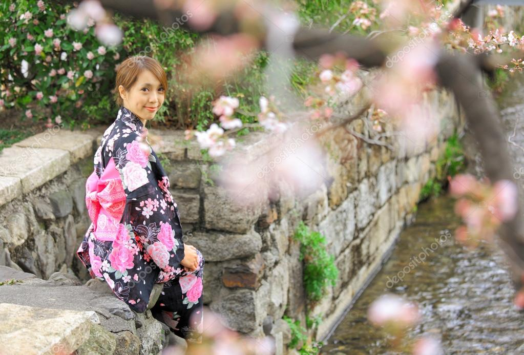 Young woman wearing Japanese kimono with cherry blossom