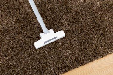 Brown carpet with vacuum cleaner