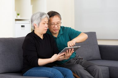 Asian old couple using tablet together