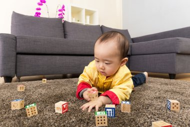 Chinese baby boy play toy blocks and lying on carpet