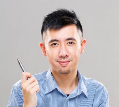 Young asian man holding pen