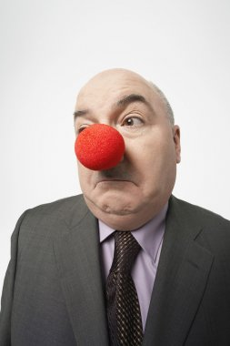 Businessman Wearing Clown Nose Frowning