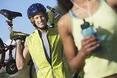 Fotografie Radfahrer trägt Fahrrad mit Frau im Vordergrund