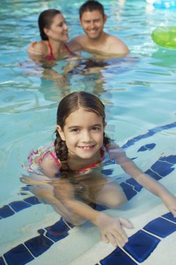 Cute Girl With Parents In Pool