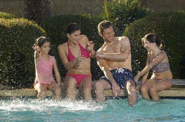 Family Having Fun At Swimming Pool