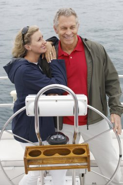 Couple Standing By Helm On Sailboat