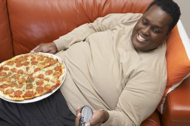 obese African American man with pizza