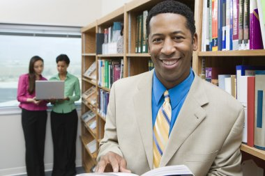 Businessman With Book In Library