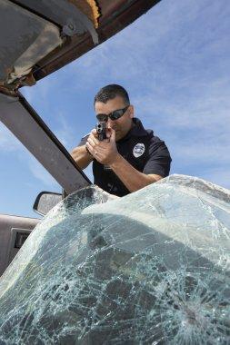 Police Officer Aiming Gun Through Broken Windshield