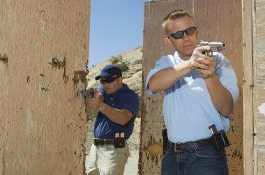 Two Officers Aiming Hand Guns At Firing Range