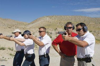 Instructor Assisting Officers At Firing Range