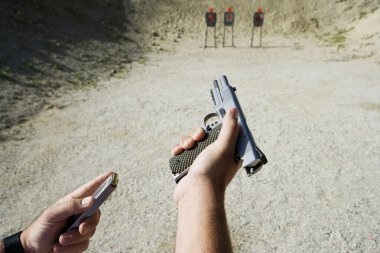 Man's Hands Loading Gun At Firing Range