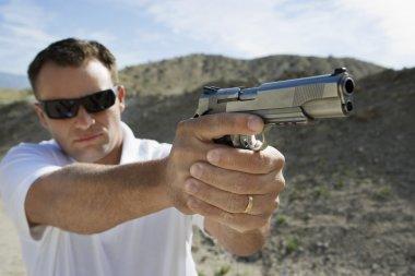 Man aiming hand gun at firing range in desert stock vector