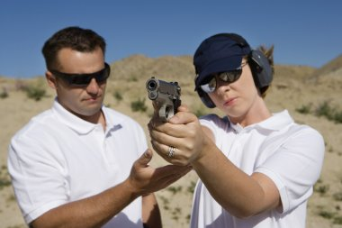 Instructor assisting woman with hand gun at firing range in desert stock vector