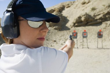 Woman Aiming Hand Gun At Firing Range
