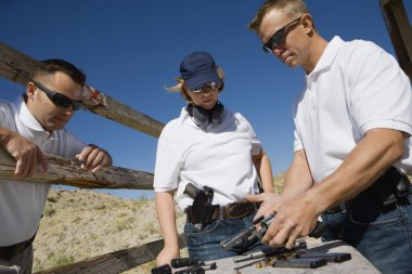 Instructor Loading Gun For Man And Woman
