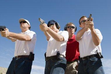 Instructor Assisting With Guns At Firing Range