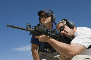 Instructor With Man Aiming Machine Gun